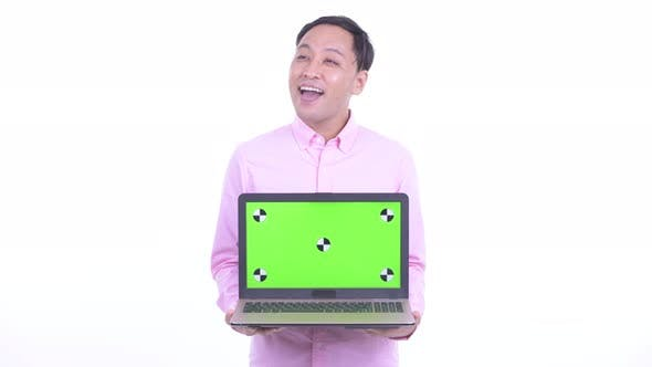 Thumbnail for Happy Japanese Businessman Thinking While Showing Laptop