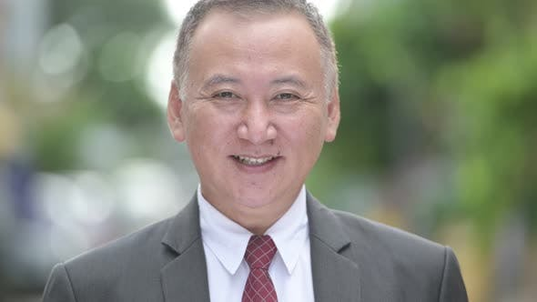 Thumbnail for Mature Happy Japanese Businessman Smiling in the Streets Outdoors