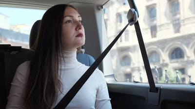 Woman Sits in Car Waiting for Driver Against Building