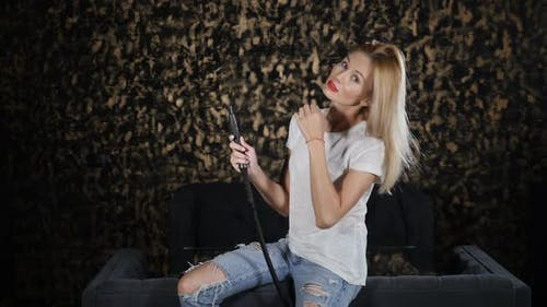 Attractive Woman Inhales and Exhales Smoke From Hookah on Dark Background