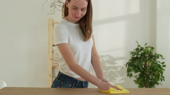 Woman Cleans the Table with a Rag