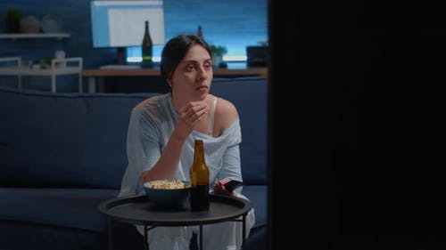 Emotional Young Woman Eating Popcorn While Watching Disgusting Tv Movie