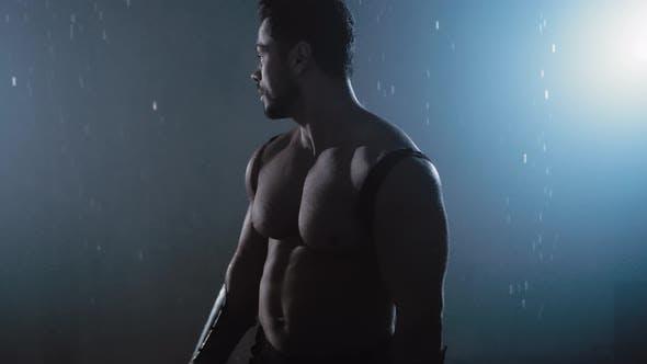 Shirtless Warrior Looking Back Under Rain