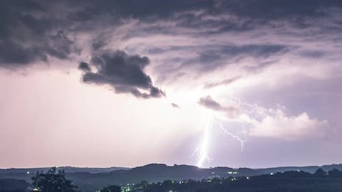 Dramatic thunderstorm with lightning discharge and rain over the hills