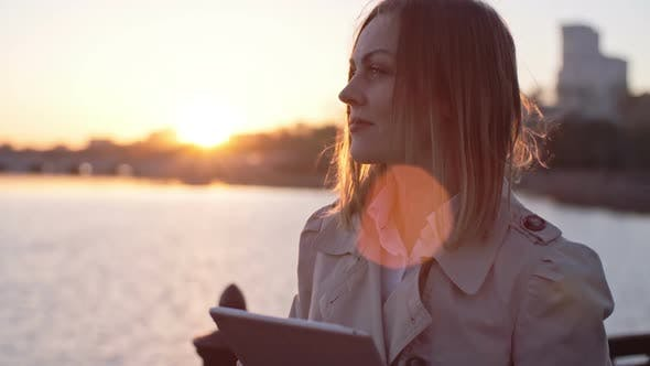 Cover Image for Woman Typing on Tablet at Sunset