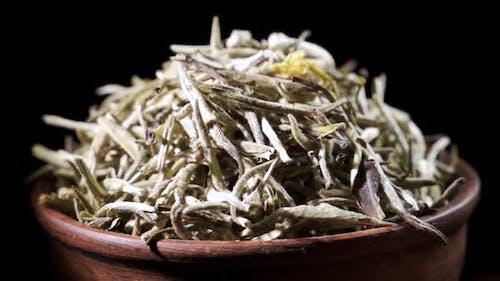 SLOW MOTION: Tea Leaves Fall on a Pile of a Green Tea - Macro Shot