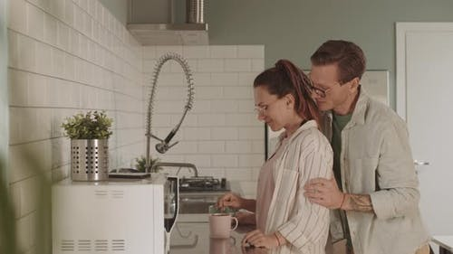 Spouses Making Coffee in Kitchen