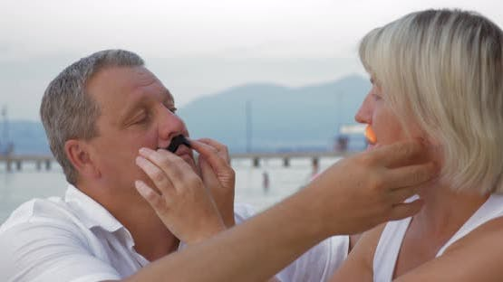 Man and woman wearing handmade moustache and having fun