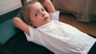 Tired Toddler in Sportswear Lies on Treadmill in Light Room