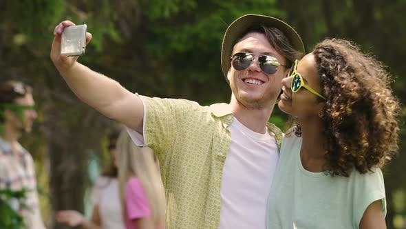 Thumbnail for Cheerful Man and Woman Smiling and Pouting to Smartphone Camera for Selfie
