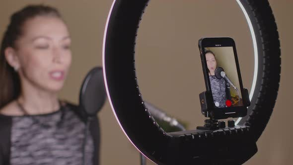 Attractive Woman Records Online Vocal Lesson Using Smartphone and Microphone