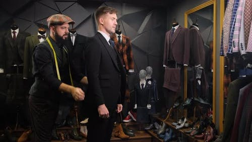 Bearded Tailor Dresses a Handsome Young Man in a Quality Handmade Suit in an Atelier. Creative Adult
