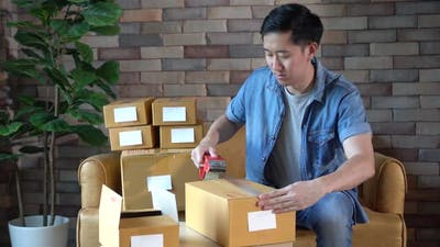 Man Packing Boxes at Home for Postal Delivery
