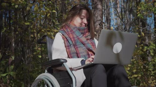 Handicapped Woman Using Laptop Outdoors