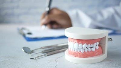 Doctor Hand Writing Prescription with Plastic Dental Teeth Model on Table