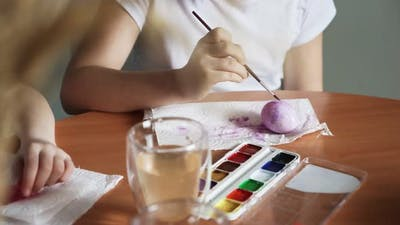 Close Up of Girls Use Paintbrushes to Paint Eggs