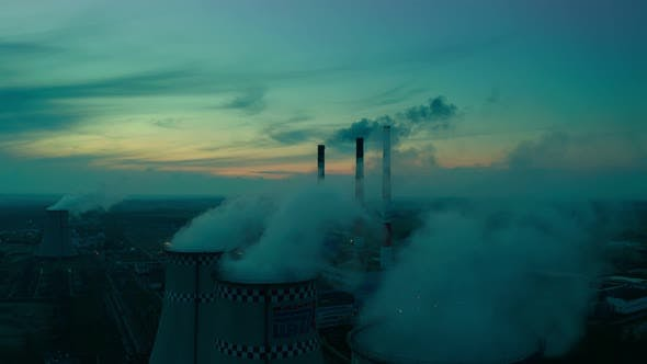Thumbnail for A bird's eye view of the plant, at sunset, large pipes of the plant release steam