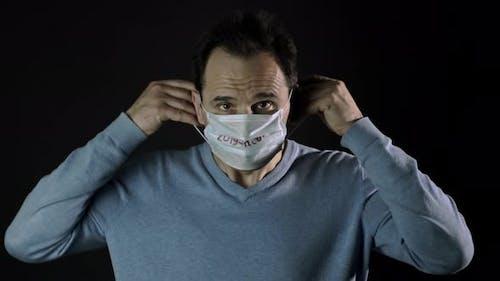 Covid-19 Concept, Man Puts on Facial Mask, Lockdown, Quarantine Restrictions