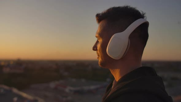 Thumbnail for Close-up of a Man in Headphones Looking at the City From the Height of a Skyscraper at Sunset. Relax