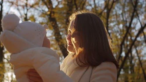 Mère avec bébé dans ses bras dans le parc en automne