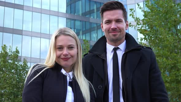 Thumbnail for A Businessman and a Businesswoman Smile at the Camera in an Urban Area - an Office Building