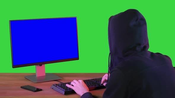 Hacker in Hood Cracking Code Using Pc on a Green Screen Chroma Key