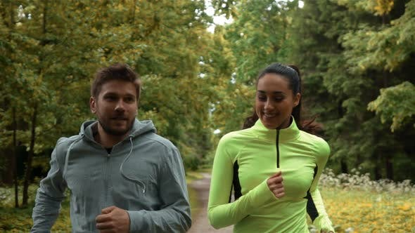 Thumbnail for Girl and Guy Communicating and Smiling During Morning Jog. They Running at the Park.