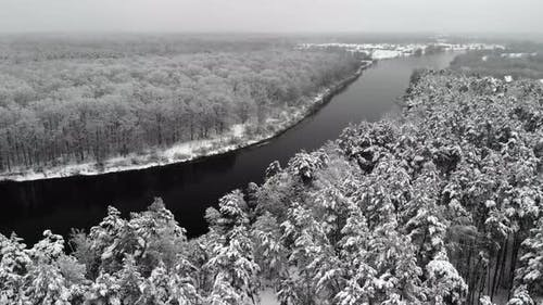 Beautiful Winter Landscape with a Dark River and Flakes of Wet White Snow on the Branches of Trees