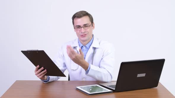 Thumbnail for Young Happy Handsome Man Doctor Explaining Something Against Wooden Table