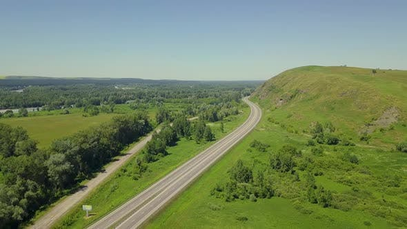 Thumbnail for Aerial: Flying Over Highway in the Highlands. View of the Tourist City, Mountain River