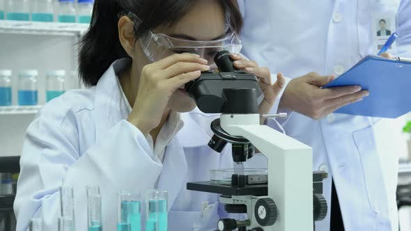 Scientist female looking microscope in laboratory