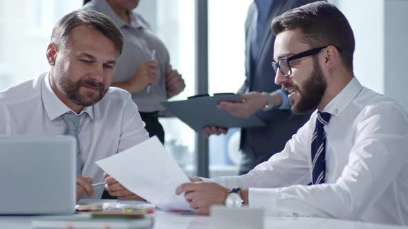 Thumbnail for Men Discussing Business Plan in Office