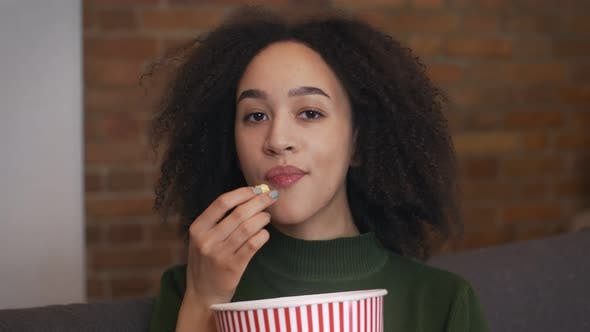 Close Up Portrait of Young African American Woman Watching Movie and Eating Popcorn Slow Motion