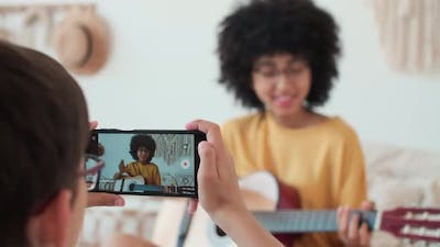Boy Films Girl While Playing Guitar