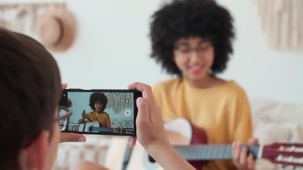 Boy Films Girl While Playing Guitar