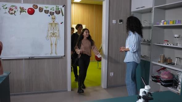 Female Teacher Greeting Pupils Entering Classroom