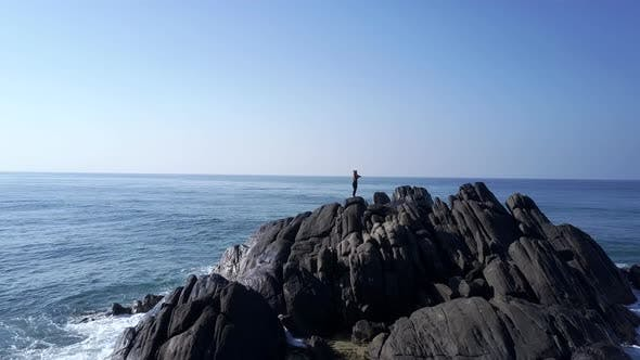 Thumbnail for Lady Silhouette Meditates on Grey Rocky Cliff Top at Ocean