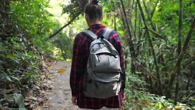 Young Woman with Backpack Walks in Lush Tropical Forest