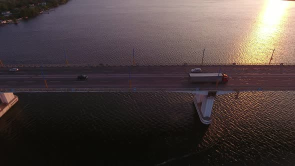 Thumbnail for Aerial Shot of a Straight River Bridge Over the Dnipro with a Shimmering Sun Path