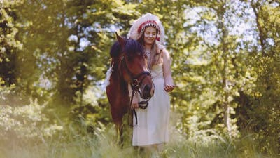 Woman In Headdress With Horse In Forest
