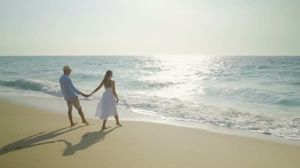 Thumbnail for Couple Holding Hands and Walking at Seaside