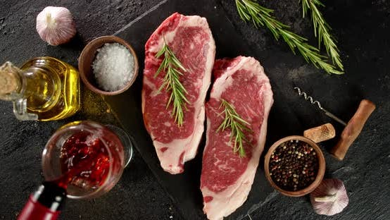 Steak Striploin Raw with Rosemary and Spices on the Table.