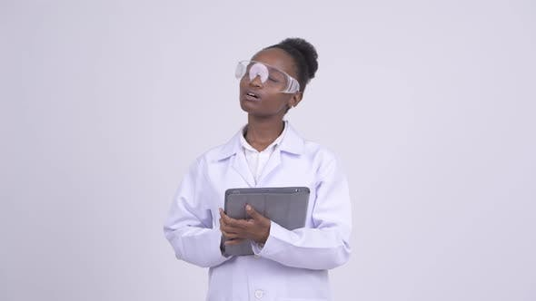 Thumbnail for Young Happy African Woman Scientist Thinking While Using Digital Tablet