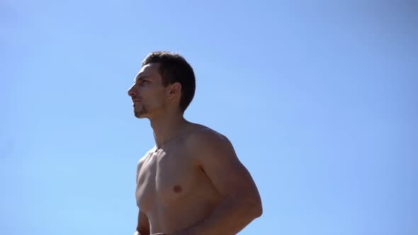 Thumbnail for Muscular Shirtless Man Running Against Blue Sky