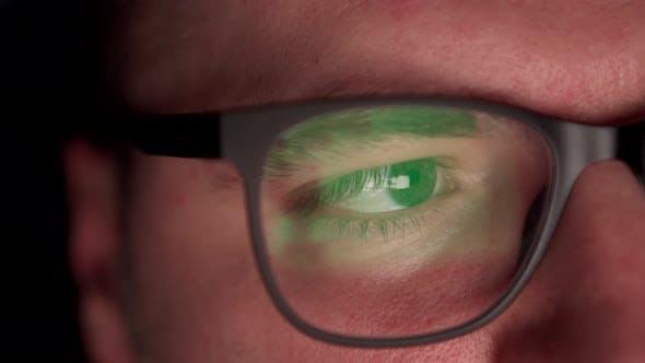 A Man Surfs the Internet, a Close-up of Glasses