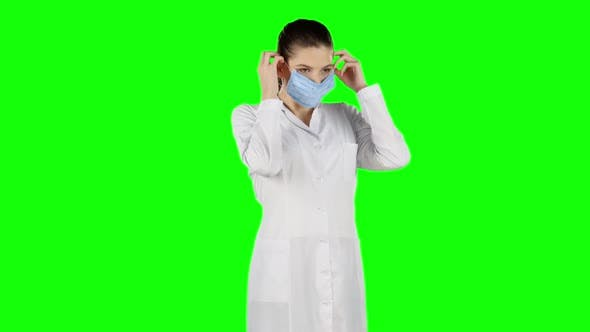 Thumbnail for Female Nurse Puts on a Blue Medical Mask. Green Screen