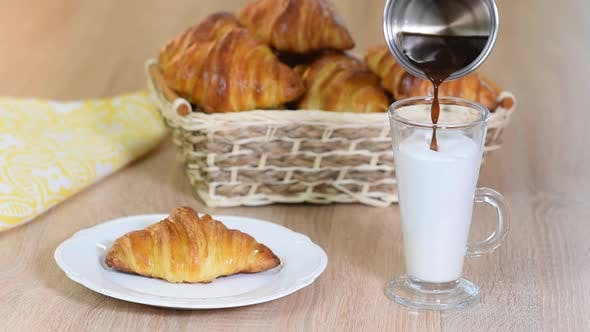 Thumbnail for Women poured espresso in a milk cup to make a latte next to butter croissant