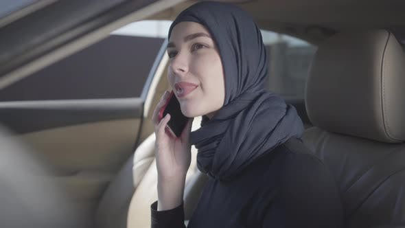 Thumbnail for Young Smiling Eastern Woman in the Modern Muslim Clothes and Beautiful Headdress Talking By