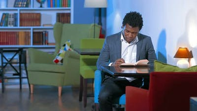 Male African Student Reading a Book in the Library