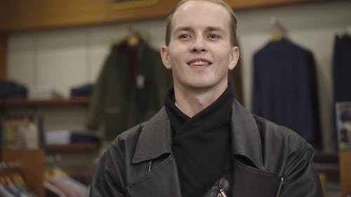 Camera Moves Down Along Man Trying on Leather Jacket in Shop. Happy Smiling Caucasian Male Shopper